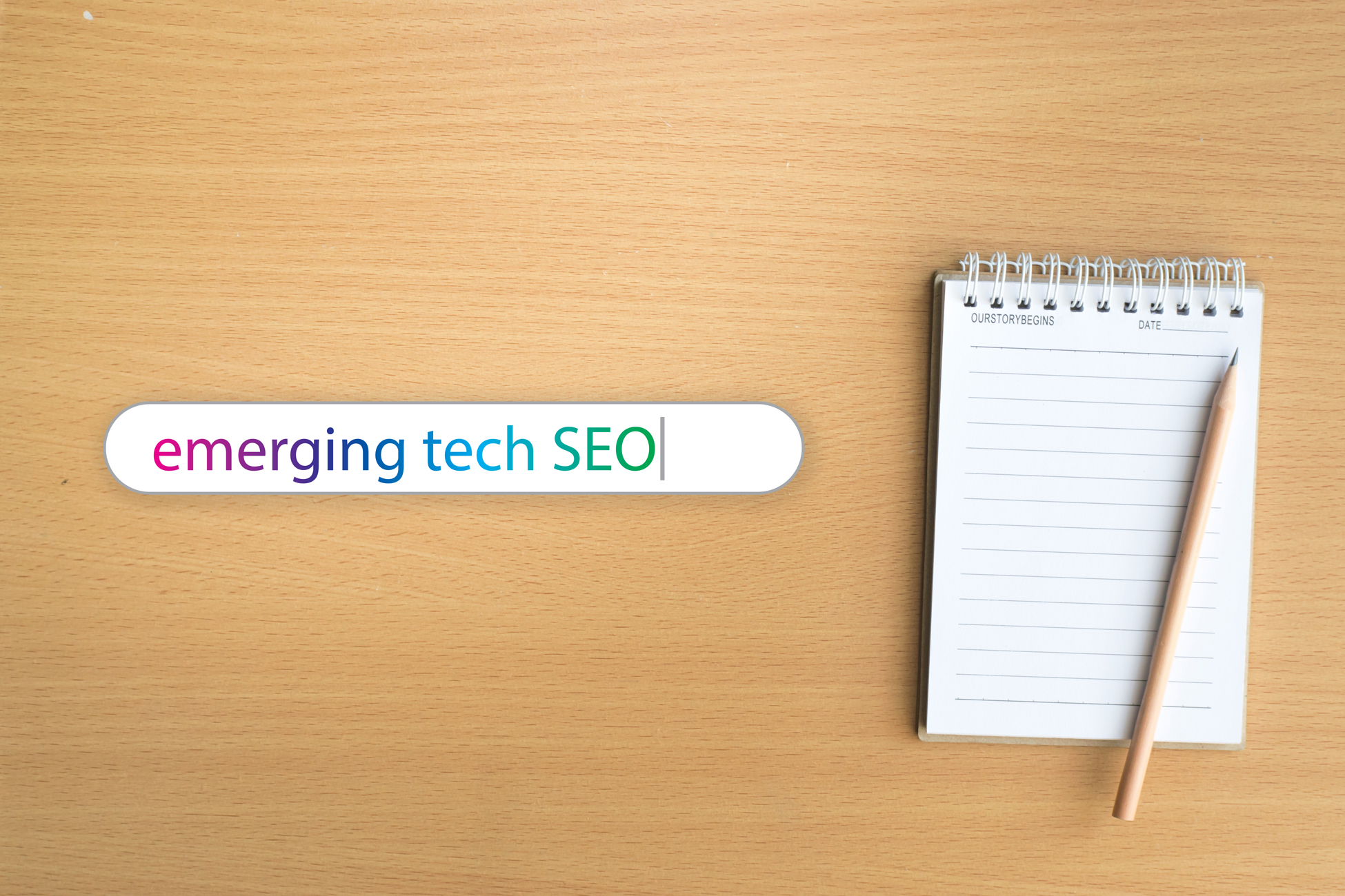 """A notebook sitting on a desk next to search bar that says """"emerging tech SEO"""""""
